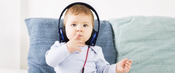 Adorable baby boy listening music at earphones.
