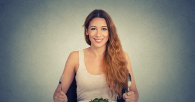 Portrait of happy woman with plate of salad, against gray wall background